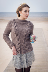 The young woman in a knitted sweater on a beach