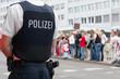 Polizist vor einer Menschenmenge - 80820439