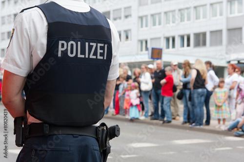 Leinwandbild Motiv Polizist vor einer Menschenmenge
