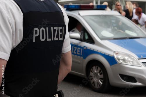 Leinwandbild Motiv Polizist und Streifenwagen vor einer Menschenmenge