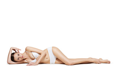 Beautiful woman with perfect body lying on white