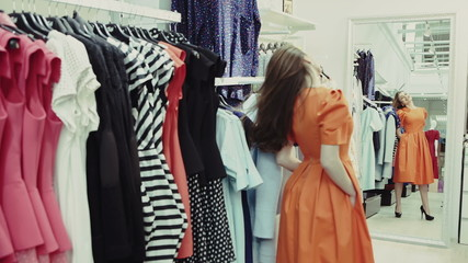Shopper woman trying clothing dress while shopping in clothes