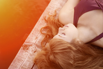 Girl lying on the wooden floor in the sunlight. Beautiful young