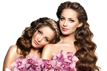 Two beauty young women, luxury long curly hair with orchid flowe