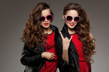 Sisters twins in hipster sun glasses laughing. Two fashion model