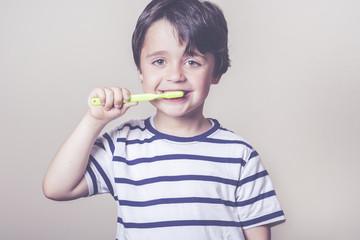 niño feliz lavandose los dientes