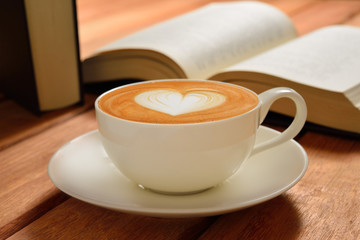 A cup of cafe latte and books on wooden table