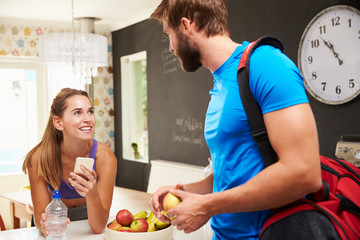 Couple Wearing Gym Clothing Talking In Kitchen