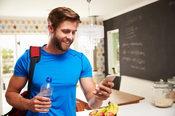 Man Wearing Gym Clothing Looking At Mobile Phone