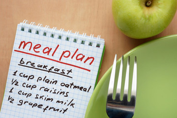 Paper with meal plan and apple. Diet concept.