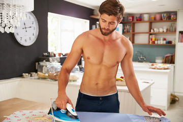 Man Standing In Kitchen Ironing Shirt