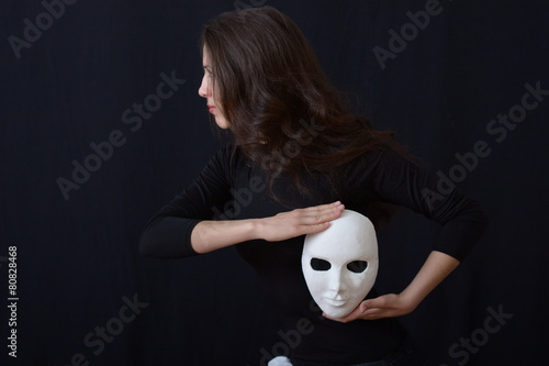 brunette girl holding a white theatrical mask - 80828468