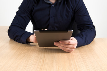 Businessman with tablet sitting at a desk