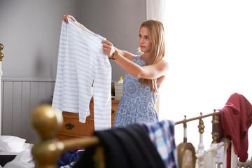 Woman In Bedroom Choosing What To Wear