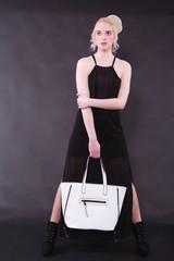 Junge blonde Frau mit weißer Tasche