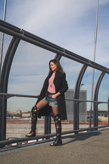 Beautiful young brunette posing on a bridge
