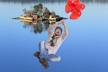 Young man flying on balloons with sea island in background