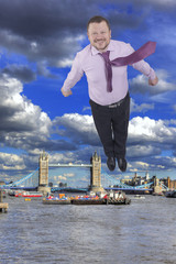 Businessman flying up with Tower bridge, London, UK in