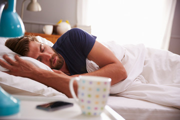 Sleeping Man Being Woken By Mobile Phone In Bedroom