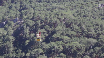 Yellow booth of a ropeway on Ai Petri rises uphill over trees