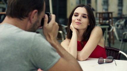 Man taking photo of his girlfriend with retro camera in cafe