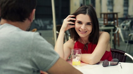 Couple sitting in cafe in city, portrait of happy woman