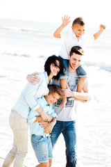 Happy Small Family Having a Vacation at the Beach During Summer.
