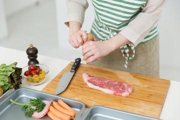 肉を料理中の女性