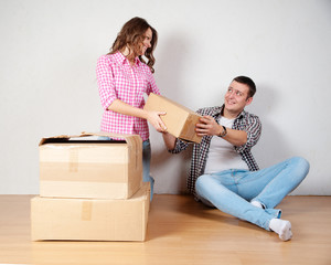 Happy young couple unpacking or packing boxes
