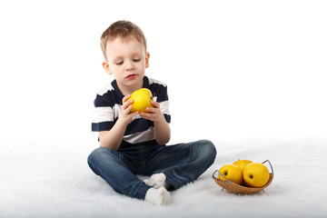 Little cute boy eating a yellow apple and smiling on white backg