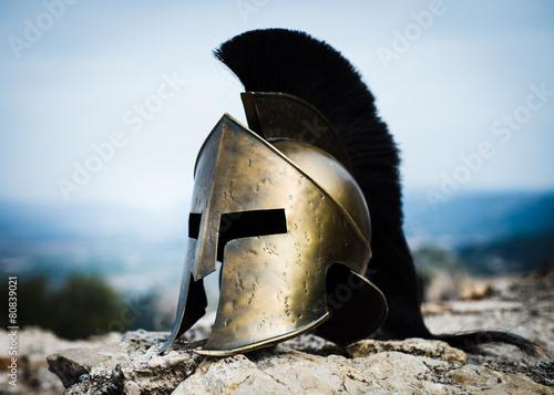 Leinwanddruck Bild Spartan helmet on rocks.