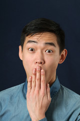 Young Asian man covering his mouth with his palm