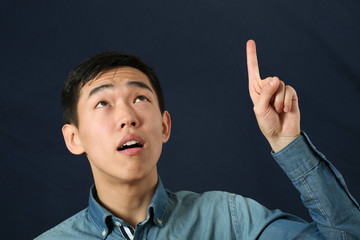 Funny young Asian man pointing his index finger and looking upwa