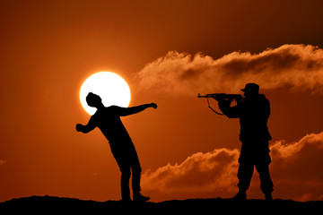 Silhouette of military soldier officer with weapons at sunset