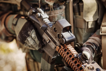 solder in gloves holding assault automatic rifle
