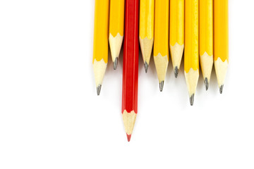 One red pencil standing out from the row of yellow pencils
