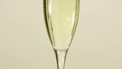 sparkling white wine in a flute gold background