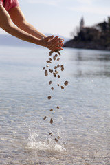 Hands dropping small stones in the sea