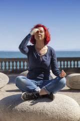 Woman performing joga on energy stones near sea coast