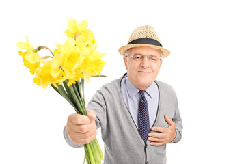 Kind senior gentleman giving flowers to someone