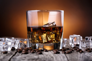Glass of whiskey with ice and coffee beans.