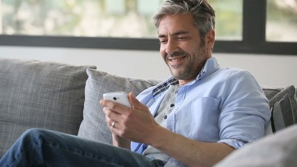 Mature man in sofa reading message on smartphone