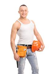 Handsome construction worker holding a helmet