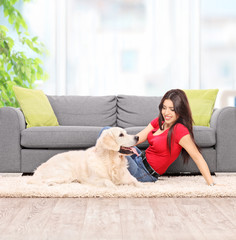 Young woman petting a dog at home