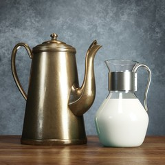 Retro jug full of milk and coffee pot on wooden surface