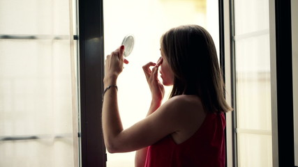 Woman checking her face in the mirror standing by window
