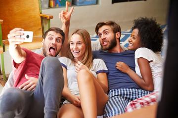 Group Of Friends Wearing Pajamas Taking Selfie On Mobile
