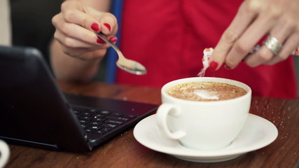 Close up of woman hands adding sugar and mixing coffee in cafe