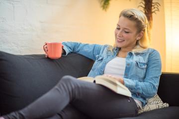 Frau sitzt auf dem Sofa mit einem Buch und einem Kaffee
