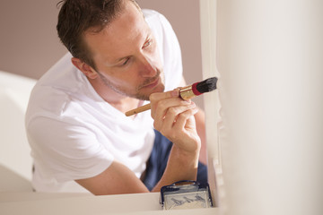 Young male painter painting indoor with paintbrush and white pai